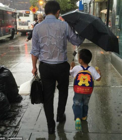 Bức ảnh bố ướt sũng khi che ô cho con khiến nhiều người xúc động
