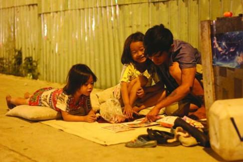 Loạt ảnh bố nuôi hai con gái trên vỉa hè gây xúc động