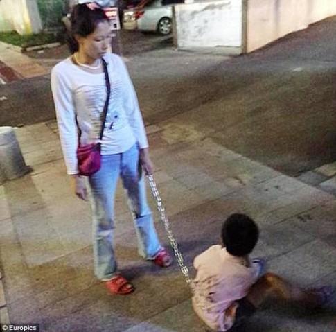 Mẹ đơn thân xích con vào xe đạp để kéo về nhà