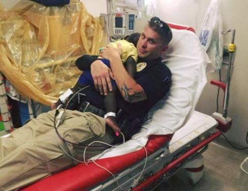 Ảnh cảnh sát vỗ về bé trai 16 tháng bị đau gây bão