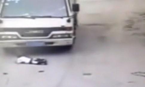 Xe tải chèn qua đứa trẻ ngồi chơi giữa đường