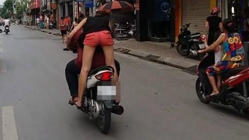 Ngồi sau xe Wave, thi thoảng cô gái cúi xuống hôn nam thanh niên đang gồng mình trước tay lái