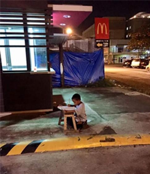 Cậu bé vô gia cư dùng ánh sáng lọt từ nhà hàng để học bài